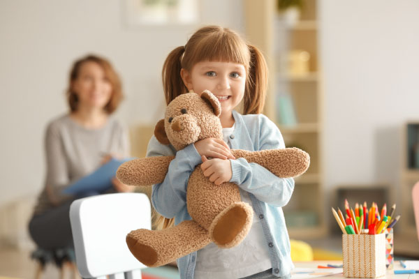 Child therapy with a happy girl holding teddy bear